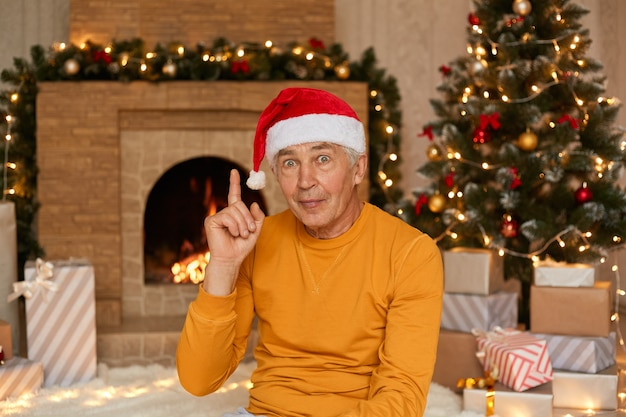 Excited mature male sitting on background of christmas tree and fireplace, , pointing finger up, has great idea, wearing yellow shirt and santa claus hat.