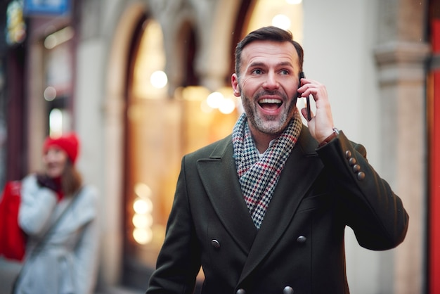 Excited mature man is on the phone