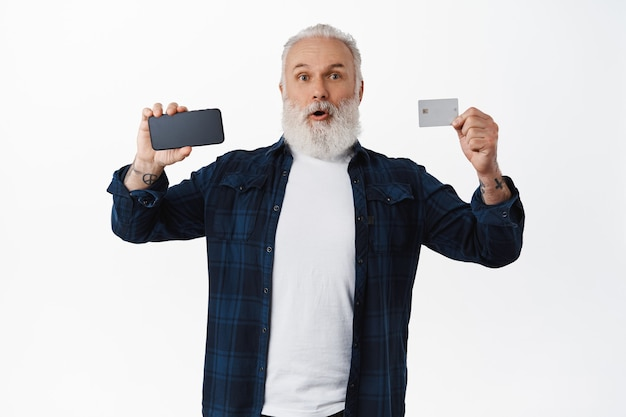 Excited mature man recommending online shopping app, contactless payment, white wall