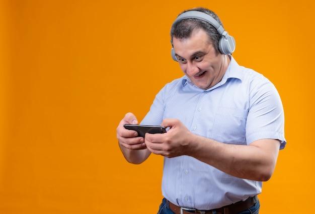 Взволнованный мужчина среднего возраста в синей полосатой рубашке играет на мобильном телефоне в наушниках стоя