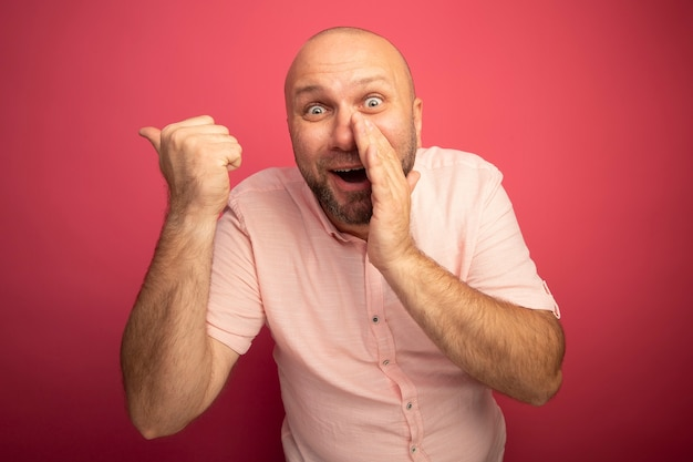 Excited middle-aged bald man wearing pink t-shirt whispers and points at side