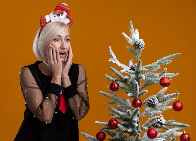 サンタクロースのヘッドバンドとネクタイを身に着けている興奮した中年のブロンドの女性は、オレンジ色の背景で隔離された側を見て顔に手を保ちながら装飾されたクリスマスツリーの近くに立っています