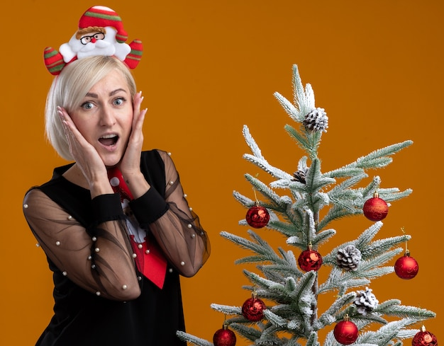 Excited middle-aged blonde woman wearing santa claus headband and tie standing near decorated christmas tree keeping hands on face looking at camera isolated on orange background