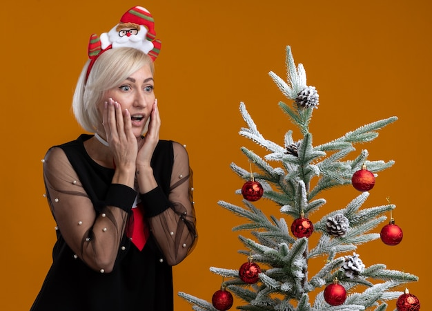 Excited middle-aged blonde woman wearing santa claus headband and tie standing near decorated christmas tree keeping hands on face looking at side isolated on orange background