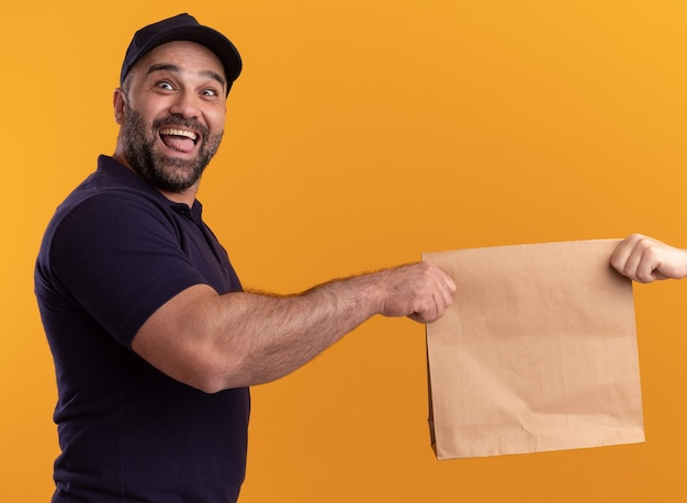 Excited middle-aged delivery man in uniform and cap giving paper food package to client isolated on yellow wall