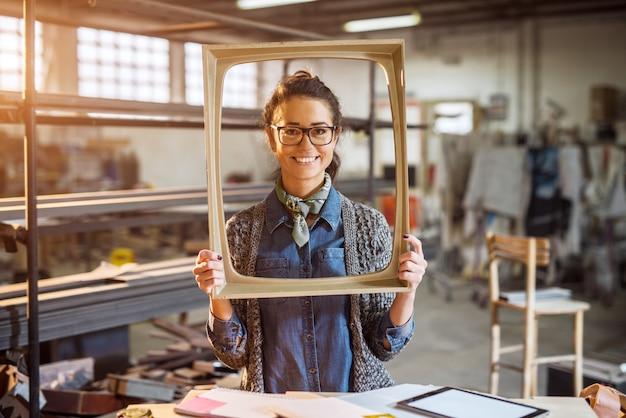 Excited пожилой инженер держа старую картинную рамку моды в солнечной мастерской ткани и представляя позади.