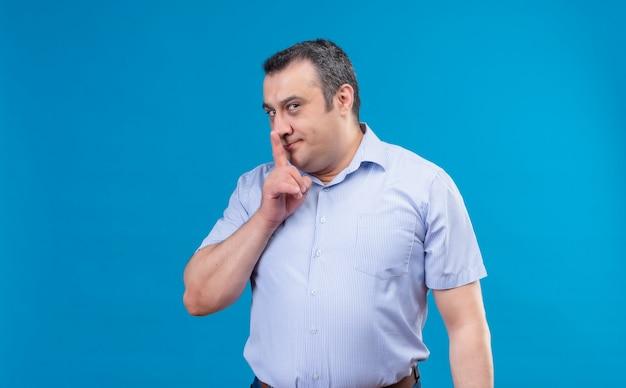 青い空間で唇にshhhサイン指を示す青いシャツを着て興奮した中年男