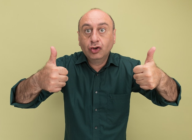 オリーブ グリーンの壁に孤立した親指を現して緑の t シャツを着た興奮した中年男性