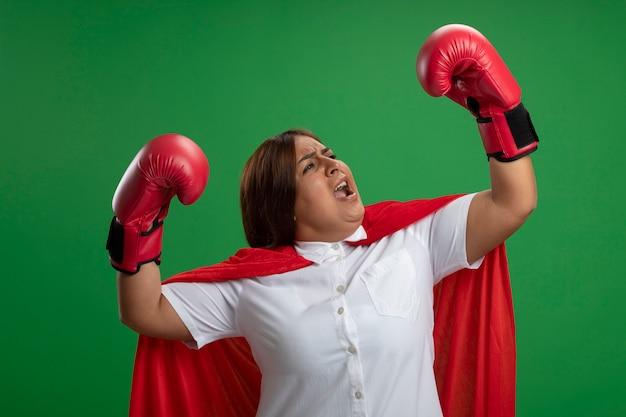 緑の背景に分離された戦闘ポーズで立っているボクシンググローブを身に着けている興奮した中年のスーパーヒーローの女性