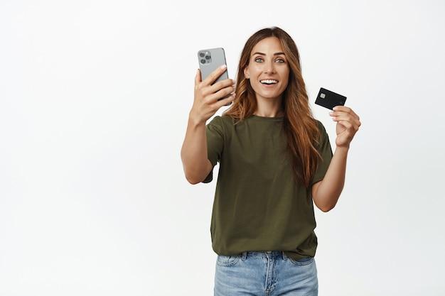 Возбужденная женщина средних лет любит делать покупки в интернете, показывает мобильный телефон и кредитную карту, довольная улыбка