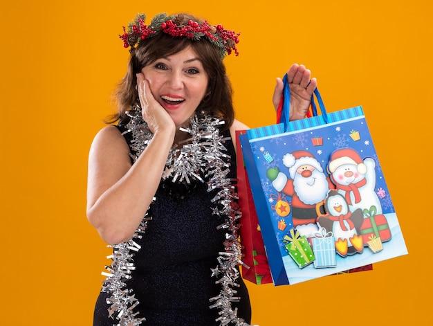 クリスマスのヘッドリースと見掛け倒しのガーランドを首に身に着けている興奮した中年の女性は、オレンジ色の壁で隔離された顔に手を保ちながらクリスマスギフトバッグを保持しています