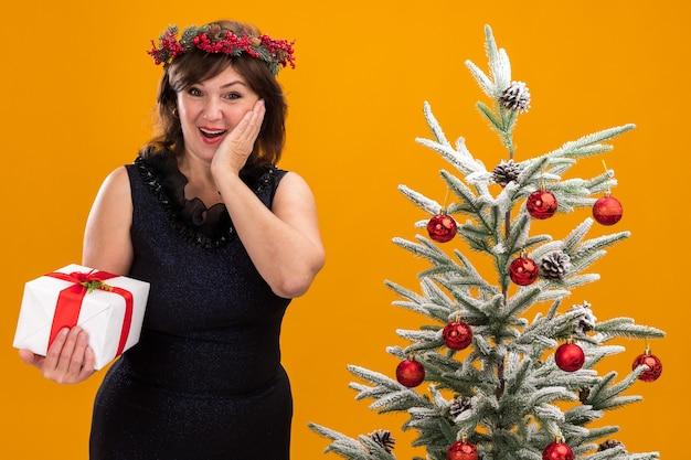Возбужденная женщина средних лет в рождественском венке и гирлянде из мишуры на шее стоит возле украшенной елки и держит подарочный пакет