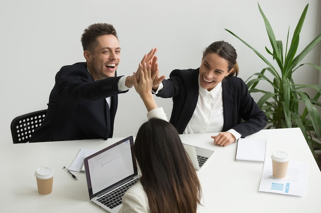 Excited millennial office team giving high five together, teambuilding concept