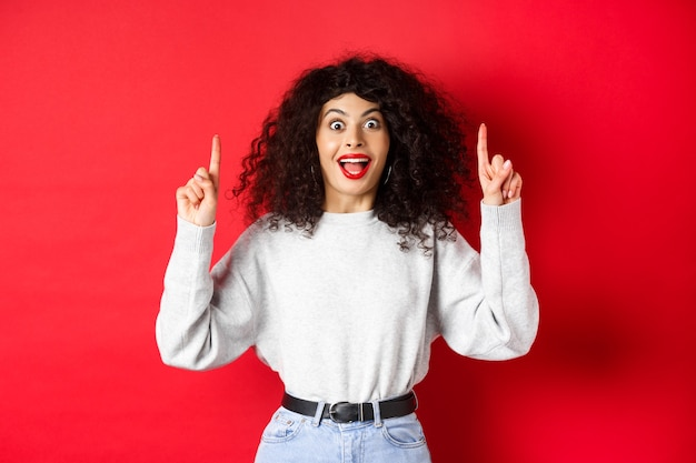 Возбужденная современная девушка показывает промо, показывает пальцами вверх и изумленно улыбается, рассказывает важные новости, стоя на красном фоне