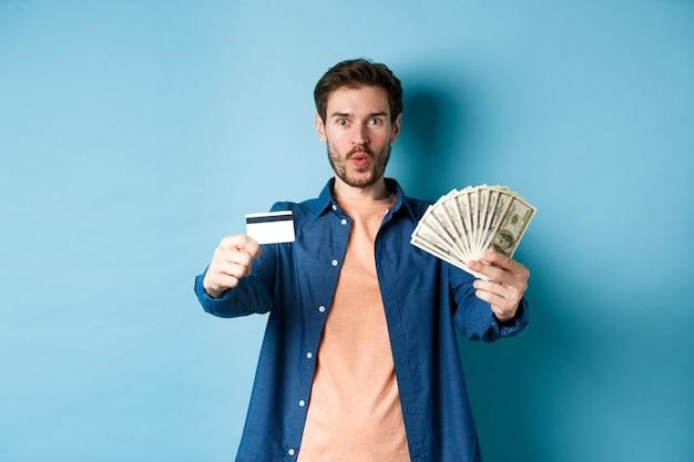 돈과 플라스틱 신용 카드를 보여주는 흥분된 현대 남자, 파란색 배경에 서서 놀랐습니다.