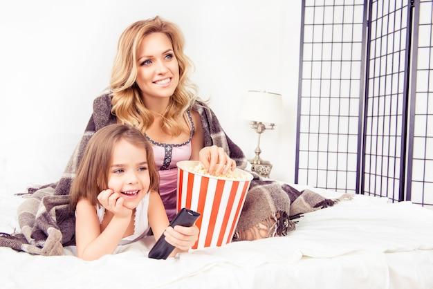 興奮したママと娘がテレビを見たり、ポップコーンを食べたり