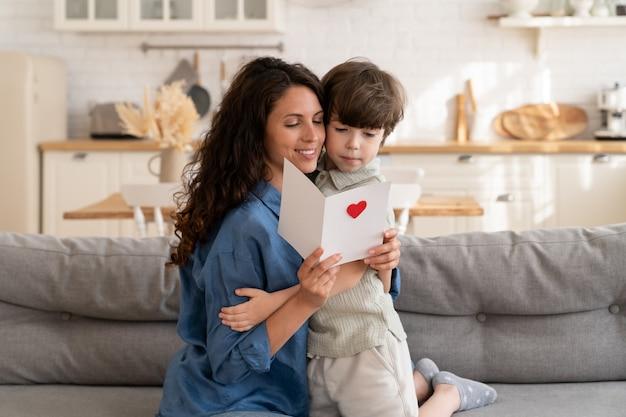 興奮したお母さんは、幼い息子からのはがきで誕生日の願いを読んで幸せな若いお母さんは就学前の子供を抱きしめます