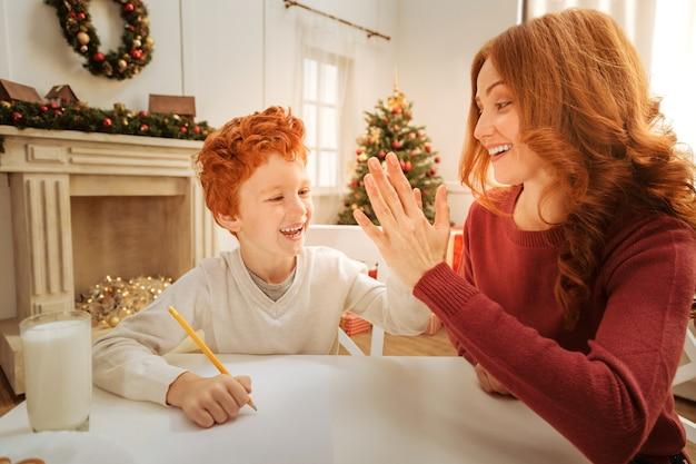 Взволнованные мать и сын широко улыбаются, давая друг другу пять и празднуя свой успех, написав письмо деду морозу.