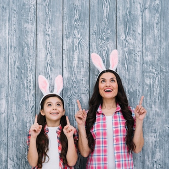 Excited mother and daughter with bunny ears pointing the finger upward against wooden backdrop