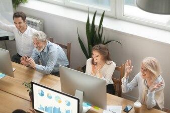興奮したやる気のある老いも若き同僚も企業の成功を祝う