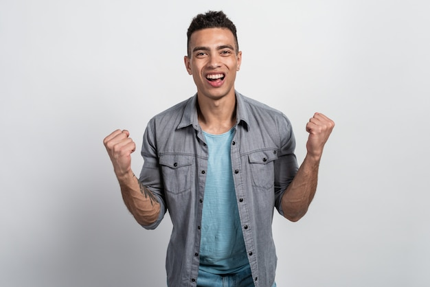Excited mulatto man shaking clenched fists, celebrating his victory or triumph