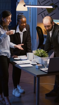 テーブル会議に立っている間に拍手する良いニュースを受け取る興奮した多民族のビジネスマン