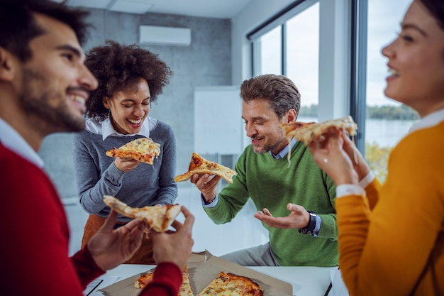 Excited multicultural group of business people standing in boardroom and eating pizza for lunch