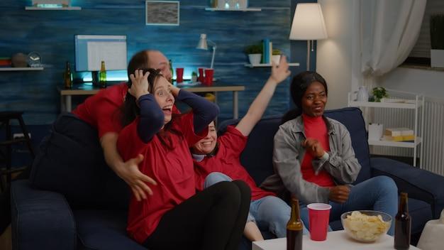 Amici multietnici eccitati che tifano insieme dopo che la squadra sportiva ha vinto il campionato di supporto wa...