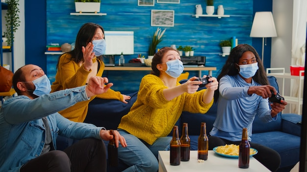 Excited multiethnic friends trying to win video games enjoying new normal party during global pandemic wearing face mask, keeping distancing sitting on couch in living room supporting women