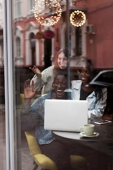 Excited multiracial friends through window