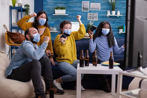 ソファに座って、保護マスクを着用した新しい通常のパーティー中にコンソールでビデオゲームをプレイする興奮した多民族ゲーマーの女性。社会的距離を保ちながらワイヤレスコントローラーを使用している友人