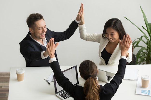 Excited multiracial team holding hands giving high five celebrating success