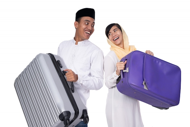 Excited muslim couple with suitcase on white background