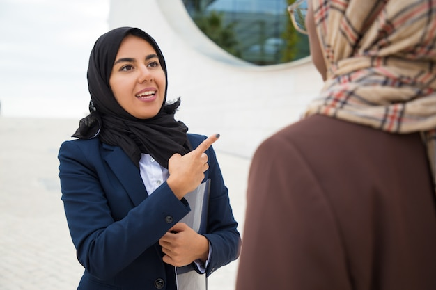 Excited muslim female employee consulting colleague outside