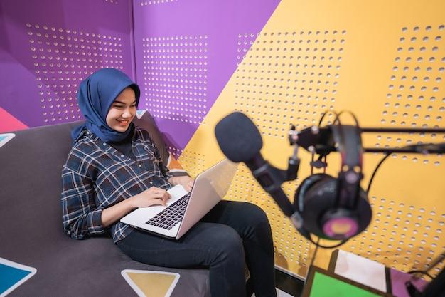 흥분한 이슬람 여성이 노트북으로 스튜디오에서 팟캐스트를 녹음하고 있다