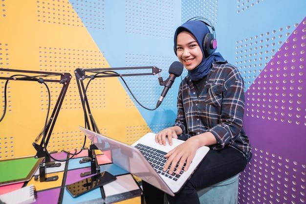 興奮したイスラム教徒の女性がラップトップを使ってスタジオでポッドキャストを録音しています