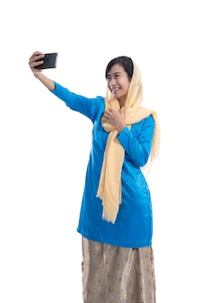 Excited muslim woman video calling using mobile smartphone