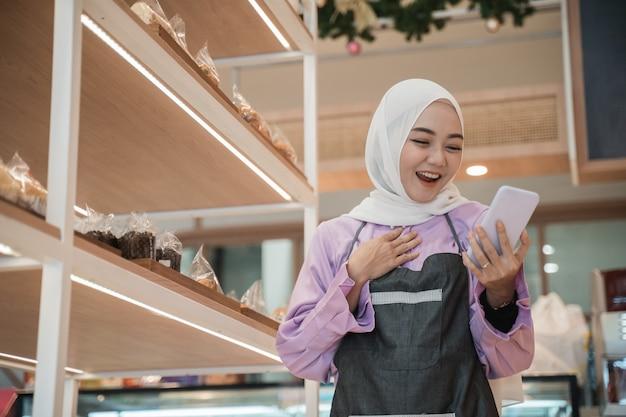 アジアのヒジャーブの女性に興奮して、彼女の電話を見ながら腕を上げます。彼女の小さな店でビジネス起業家