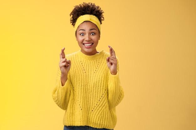 黄色いセーターを着た興奮した楽観的な希望に満ちた若い臆病なアフリカ系アメリカ人の女の子は、良いニュースを期待して広く興奮して笑っています。