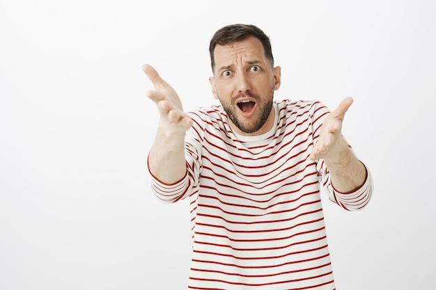 Возбужденный чрезмерно эмоциональный футбольный фанат в полосатом пуловере, протягивая руки к