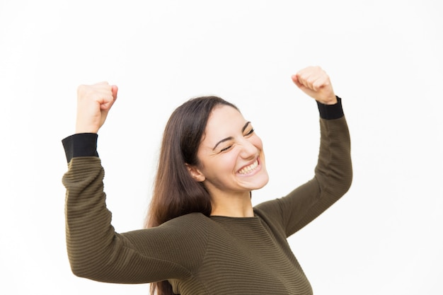 Excited overjoyed beautiful latin woman making winner gesture