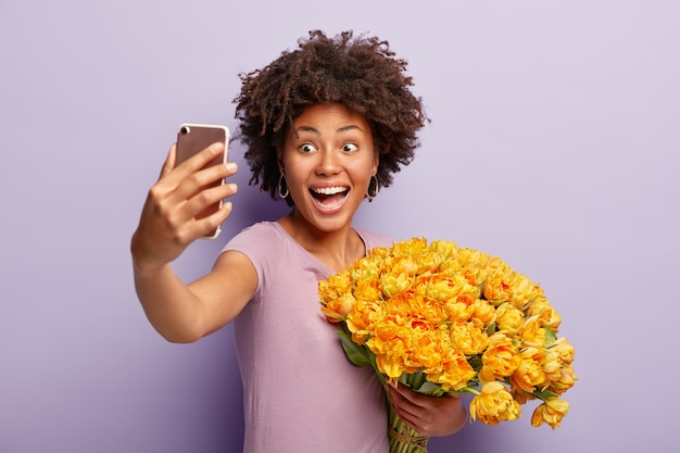 흥분된 너무 기뻐서 어두운 피부를 가진 여성이 스마트 폰으로 셀카를 찍고 튤립 꽃다발을 들고 있습니다.