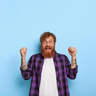 파란색 벽에 포즈를 취하는 흥분된 기뻐 세련된 생강 남자