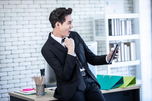사무실 배경, 비즈니스 성공에서 테이블 작업을 들고 젊은 아시아 사업가 비명을 지르는 성공적인 느낌의 승자가 흥분한