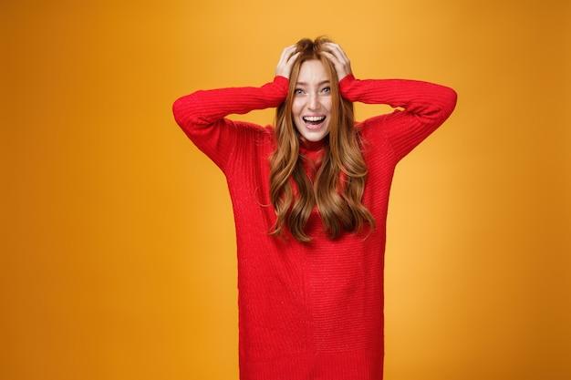 Eccitata e sopraffatta affascinante donna dai capelli rossi in abito rosso caldo lavorato a maglia che urla dal brivido e dalla felicità tenendosi per mano sui capelli sorridendo ampiamente impressionata da una fortuna inaspettata sul muro arancione