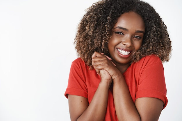Excited and overwhelmed cute amused dark-skinned womanfriend in red t-shirt smiling broadly pressing palms together near chest standing thrilled and thankful for awesome gift over white wall