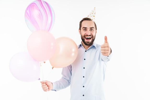 Возбужденный тусовщик держит воздушные шары и показывает палец вверх изолированно над белой стеной