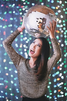 Excited partying young woman with disco ball