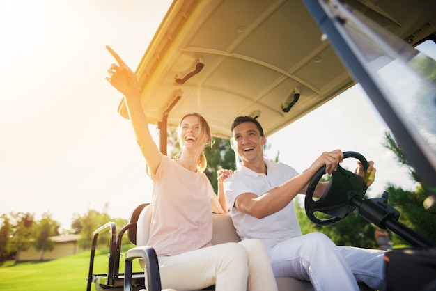 Excited people couple driving golf car on course.