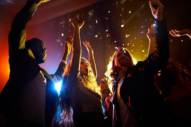Возбужденные люди танцуют на концерте в ночном клубе